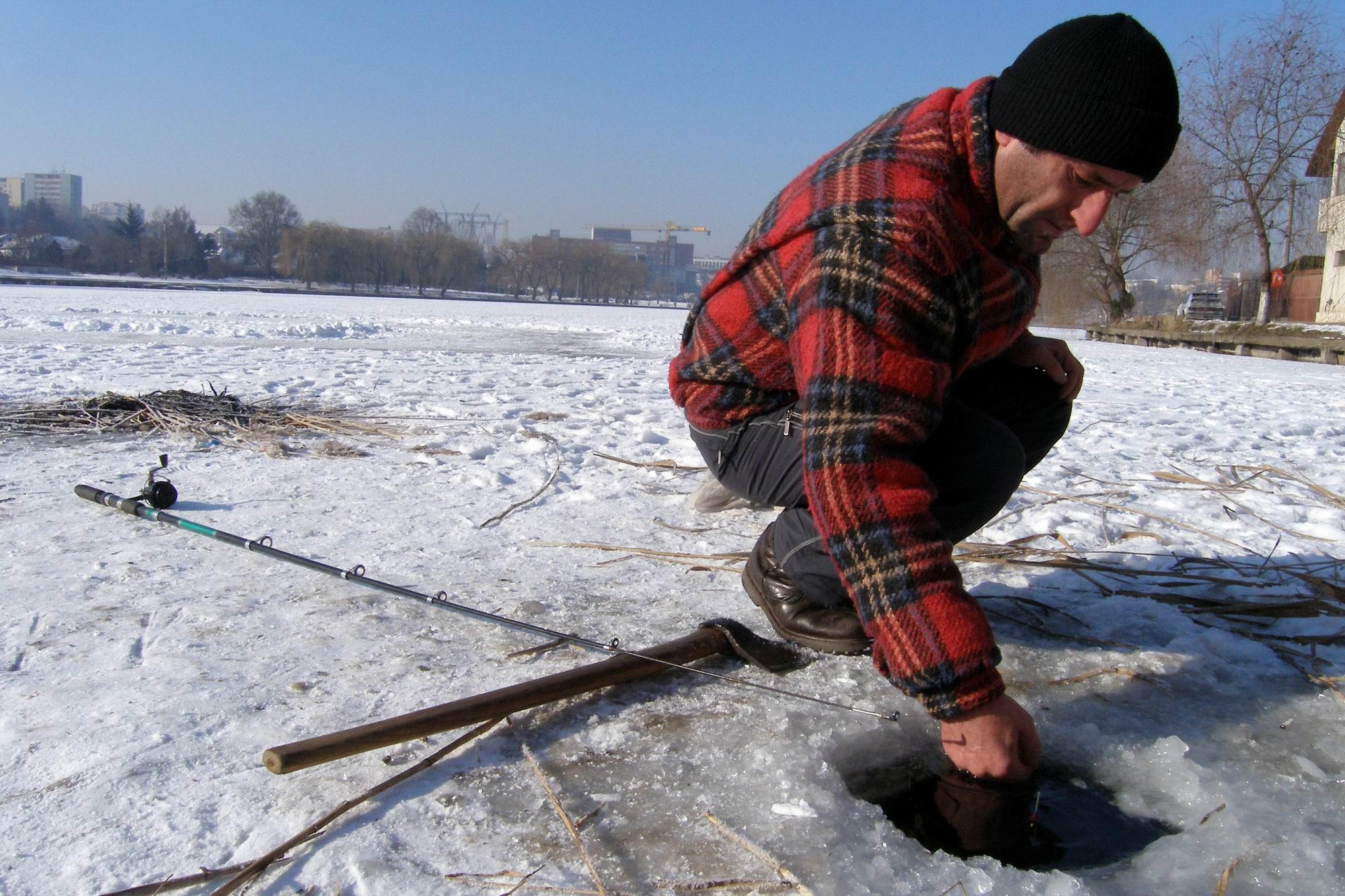 Uni pescar clujean curata gheata din copca, miercuri 25.01.2006,  in gheata groasa de peste 20cm, pe un lac din cartierul clujean Marasti. In cursul acestei dimineti s-au interistrat la Cluj-Napoca temperaturi de - 20 gradde Celsius.