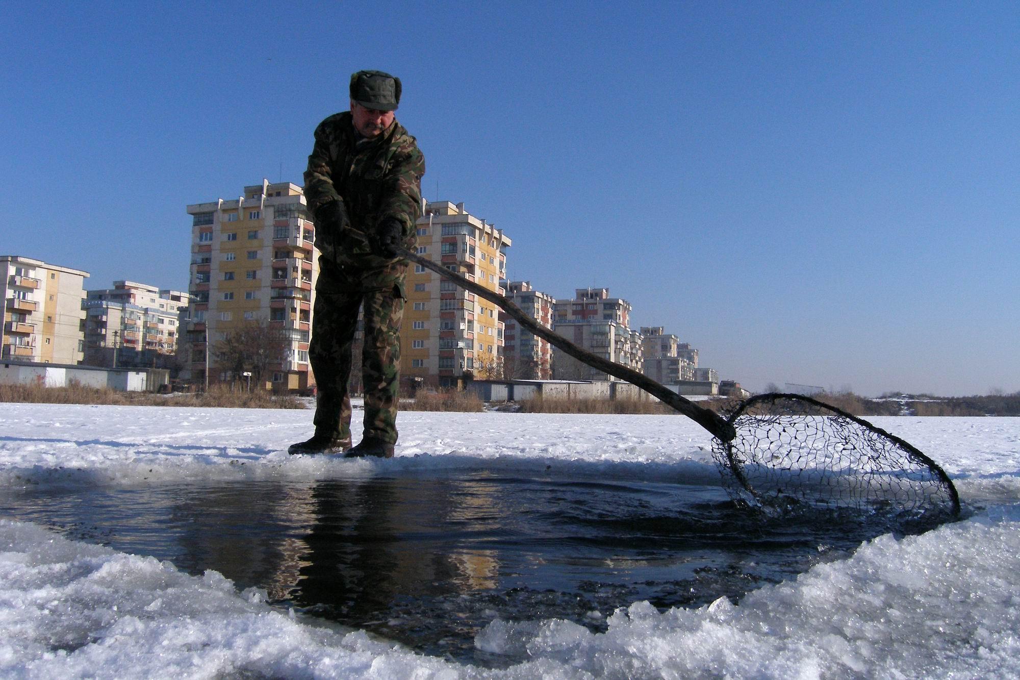 Un angajat de la AGVPS Cluj curata de gheata, miercuri 25.01.2006, o copca taiata in gheata groasa de peste 20cm, pe un lac din cartierul clujean Marasti. In cursul acestei dimineti s-au interistrat la Cluj-Napoca temperaturi de - 20 gradde Celsius
